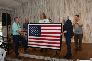TJ Wright holds up a framed US Flag